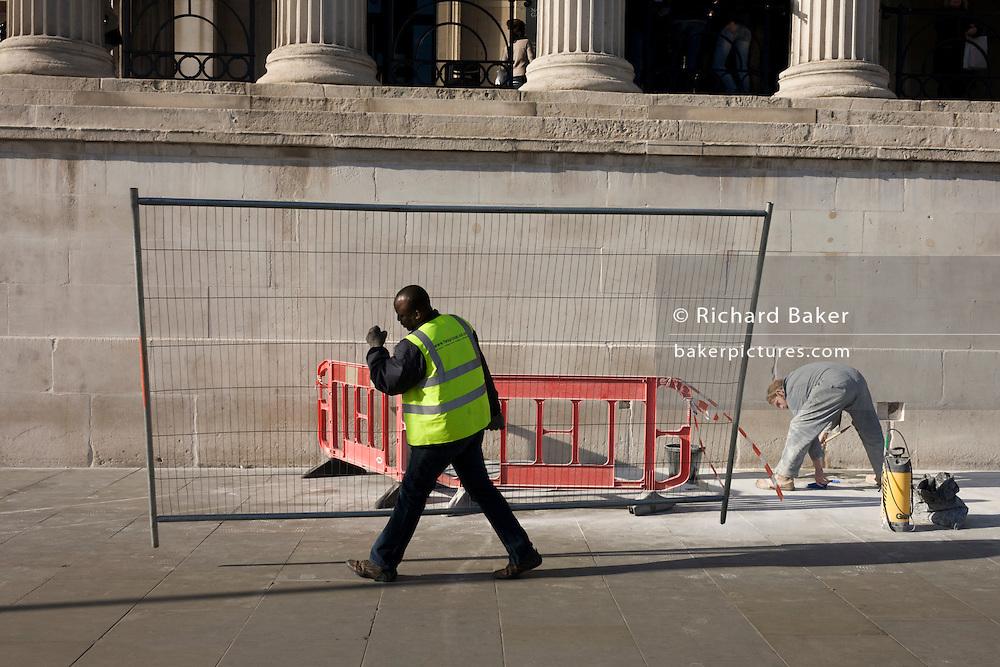 Workman carries construction fencing panel past bending maintenance man in Trafalgar Square.