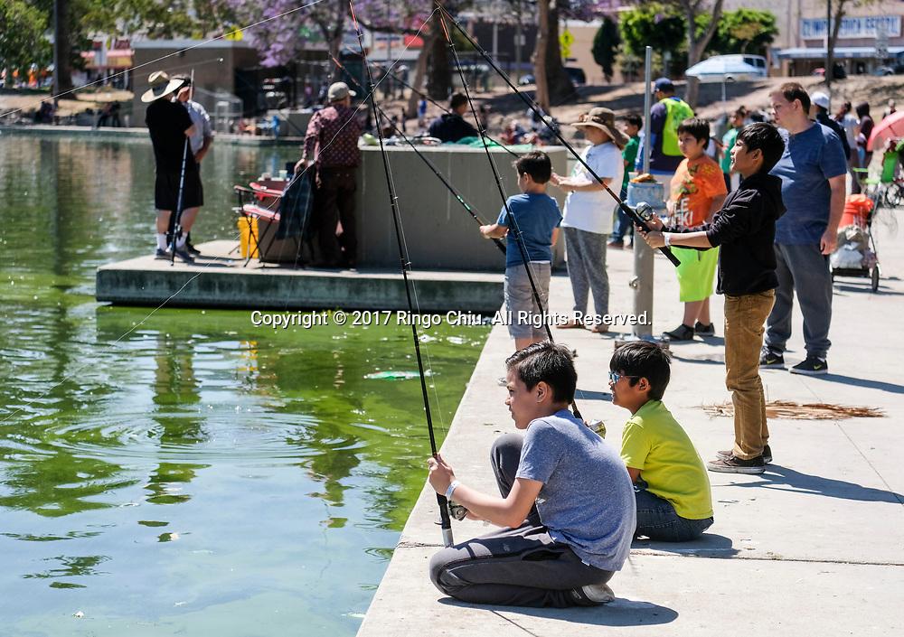 5月13日,孩子专心钓鱼。当日,在美国加利福尼亚州洛杉矶,洛杉矶市康乐与公园局在市中心附近的麦克阿瑟公园举办免费青少年儿童钓鱼日活动。所有15岁以下的孩子,都可得到免费的钓鱼训练、鱼竿与鱼饵。新华社发 (赵汉荣摄)<br /> Children fish during a youth fishing derby held by the Los Angeles Department of Recreation and Parks, in the lake at MacArthur Park near downtown Los Angeles, the United States on May 13, 2017. (Xinhua/Zhao Hanrong)(Photo by Ringo Chiu/PHOTOFORMULA.com)<br /> <br /> Usage Notes: This content is intended for editorial use only. For other uses, additional clearances may be required.