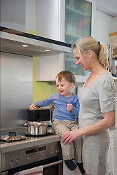 Boy helping his mother stirring food in pot, smiling