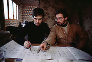 Mark Loizeaux & Steve Pettigrew review plans for placement of explosives. Controlled Demolition, Inc, used explosives to demolish an aging housing project near Paris. The Loizeaux brothers run the world's most famous demolition company founded by their father. Mark Loizeaux films and watches the demolition as his brother Doug pushes the detonation controller. La Courneuve, France. MODEL RELEASED..