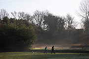 People out walking their dog in beautiful sunlight breaks through morning mist through trees in Highbury Park in Moseley / Kings Heath in Birmingham, United Kingdom.
