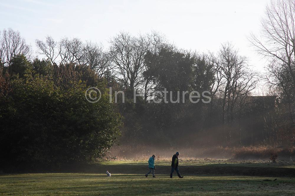 People out walking their dog in beautiful sunlight breaks through morning mist through trees in Highbury Park in Moseley / Kings Heath in Birmingham, United Kingdom.