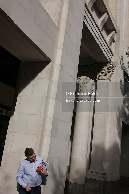 Educated man looks at the cover of his book with City of London sculpture.