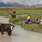 Yaks and people at a stream in Tibet. Asia<br /> EDITORIAL USE ONLY - MODEL RELEASE N/A