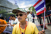 """27 AUGUST 2013 - BANGKOK, THAILAND: A Thai """"Yellow Shirt"""" royalist walks past the British embassy in Bangkok. About 25 people, including at least two British citizens, picketed the embassy Tuesday morning. They were protesting against former British Prime Minister Tony Blair, who is expected to speak to a political reform commission established by Thai Prime Minister Yingluck Shinawatra. The protest leaders were invited in to the Embassy grounds to speak to representative of the British government. The protest disbanded afterwards. No one was arrested during the protest, which lasted a little over an hour.       PHOTO BY JACK KURTZ"""