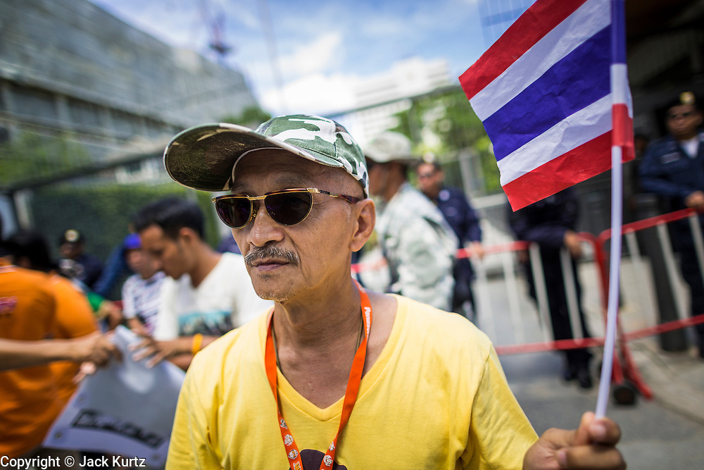 "27 AUGUST 2013 - BANGKOK, THAILAND: A Thai ""Yellow Shirt"" royalist walks past the British embassy in Bangkok. About 25 people, including at least two British citizens, picketed the embassy Tuesday morning. They were protesting against former British Prime Minister Tony Blair, who is expected to speak to a political reform commission established by Thai Prime Minister Yingluck Shinawatra. The protest leaders were invited in to the Embassy grounds to speak to representative of the British government. The protest disbanded afterwards. No one was arrested during the protest, which lasted a little over an hour.       PHOTO BY JACK KURTZ"