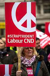 © Licensed to London News Pictures. 26/02/2016. London, UK. A woman carrying an anti trident Labour CND banner as Thousands of people take part in a CND (Campaign for Nuclear Disarmament) rally in central London on February 27, 2016. Expected to attend the event are Labour leader Jeremy Corbyn,  leader of the SNP Nicola Sturgeon and Plaid Cymru's Leanne Wood. Photo credit: Ben Cawthra/LNP