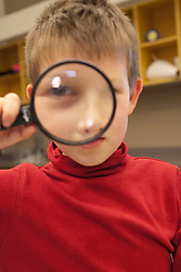 United States, Washington, Bellevue, boy (age7) with magnifying glass.  MR