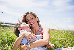 Woman with her son playing on grass and enjoying picnic, Bavaria, Germany