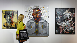 "© Licensed to London News Pictures. 04/10/2019. LONDON, UK. A visitor views ""Terry"" by Matt Small at the JG Contemporary stand at Moniker International Art Fair, an urban contemporary art fair taking celebrating its 10 year anniversary in the UK.  The fair is  place at Chelsea's Sorting Office air until 6 October 2019.  Photo credit: Stephen Chung/LNP"