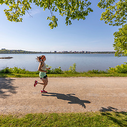 A woman jogging on the Back Cove Trail next to Back Cove in Portland, Maine.