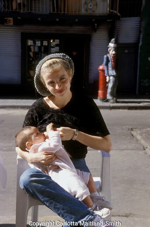 Mother breastfeeding in the street in la Boca Buenos Aires Argentina.