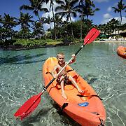KAUAI, HI, July 13, 2007: A young boy enjoys kayaking a saltwater lagoon at the Hyatt Regency Kauai Resort and Spa on Kauai.