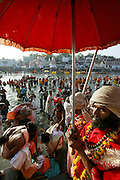 Sadhus (Hindu ascetics) congregate to bathe in the Shipra River during the Kumbh Mela festival, Ujjain, Madhya Pradesh, India. The Kumbh Mela festival is a sacred Hindu pilgrimage held 4 times every 12 years, cycling between the cities of Allahabad, Nasik, Ujjain and Hardiwar.  Participants of the Mela gather to cleanse themselves spiritually by bathing in the waters of India's sacred rivers.  Kumbh Mela is one of the largest religious festivals on earth, attracting millions from all over India and the world.  Past Melas have attracted up to 70 million visitors.