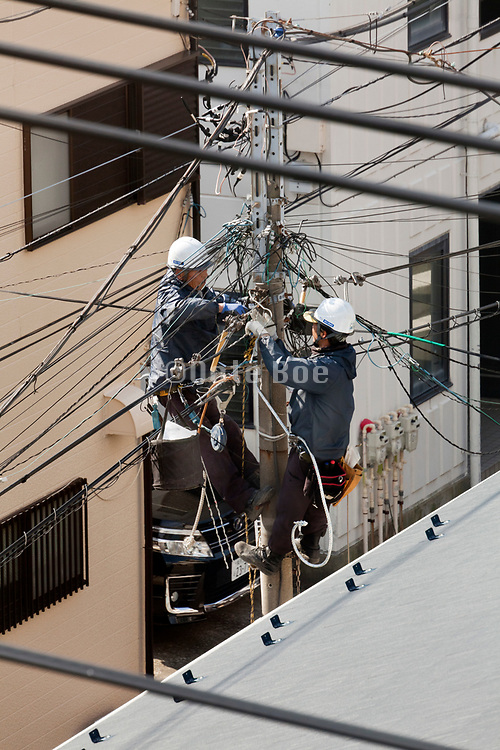 workers doing maintenance work on the above ground utility net  cables in Japan