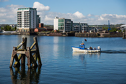 Cardiff, UK. 2nd May, 2017. A small boat passes in front of modern apartment blocks at Cardiff Docks.