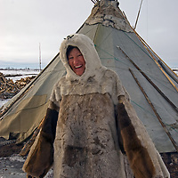"""North of the Arctic Circle in Russia, Katerina (""""Katya"""") Vaucheskaya, a member of the last nomadic Komi reindeer herding clan, stands in front of her chum (tepee), wearing a traditional reindeer skin malitsa robe with mittens sewed to the ends of its sleeves."""
