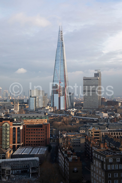 Cityscape skyline view over rooftops in Southwark and London Bridge towards The Shard and in the distance the financial district and skyscrapers at Canary Wharf in London, England, United Kingdom. The Shard, also referred to as the Shard of Glass, Shard London Bridge and formerly London Bridge Tower, is an 87-storey skyscraper in London that forms part of the London Bridge Quarter development.