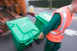 Binman returning neighbourhood wheelie bins after unloading them into dust cart,