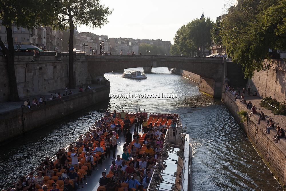France. Paris.  people enjoying sunset on the quay notre dame, by the seine river Paris / les gens se pressent sur le quai notre dame pour profiter du soleil. Paris  at sunset