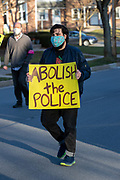 """A protester holds a sign reading """"abolish the police."""""""