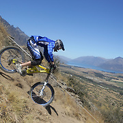 Russell Archer from Wellington in action during the New Zealand South Island Downhill Cup Mountain Bike series held on The Remarkables face with a stunning backdrop of the Wakatipu Basin. 150 riders took part in the two day event. Queenstown, Otago, New Zealand. 9th January 2012. Photo Tim Clayton