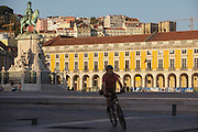 Biker cycling at Terreiro do Paço, also know as Praça do Comércio (Commerce Square). This square is the largest in Lisbon and is located just by the river Tagus. From left to right can be seen the equestrian statue of King Joseph I , on the top of the hill, Saint George Castle and at righmost the Old Cathedral.