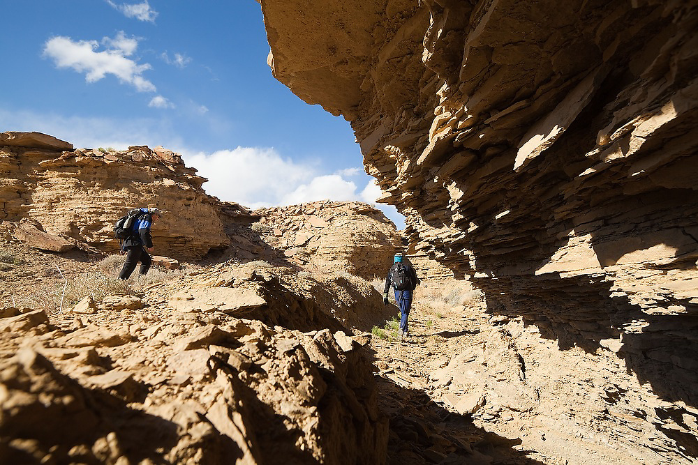 Students on a geology field trip with the University of Colorado climb through Muddy Creek canyons near Hanksville in Southern Utah.