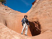 Tom explores Halfway Hollow plunge pool, along trail to Zebra Slot Canyon, Grand Staircase Escalante National Monument, Utah, USA. Directions to unmarked trailhead for Zebra and Tunnel Slot Canyons: From Escalante town, drive 6 miles east on Highway 12, turn right on Hole-in-the-Rock Road, drive 7.8 miles to the third cattle guard and park on west side of road. Hike east on well-trodden but unmarked path, 5 miles round trip to Zebra Slot, plus an optional 3 miles round trip to Tunnel Slot (750 feet gain over 8 miles), using map from GSENM Visitor Center or canyoneeringusa.com. For licensing options, please inquire.