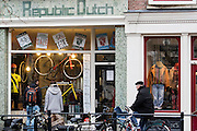 In Utrecht kijken een man en vrouw in de etalage van de fietswinkel Republic Dutch waar momenteel uitverkoop is. Het merk maakt duurzame fietsen op maat. <br /> <br /> In Utrecht a man and woman are watching in the window of the bike shop where Dutch Republic is currently on sale. The brand makes durable custom bikes.