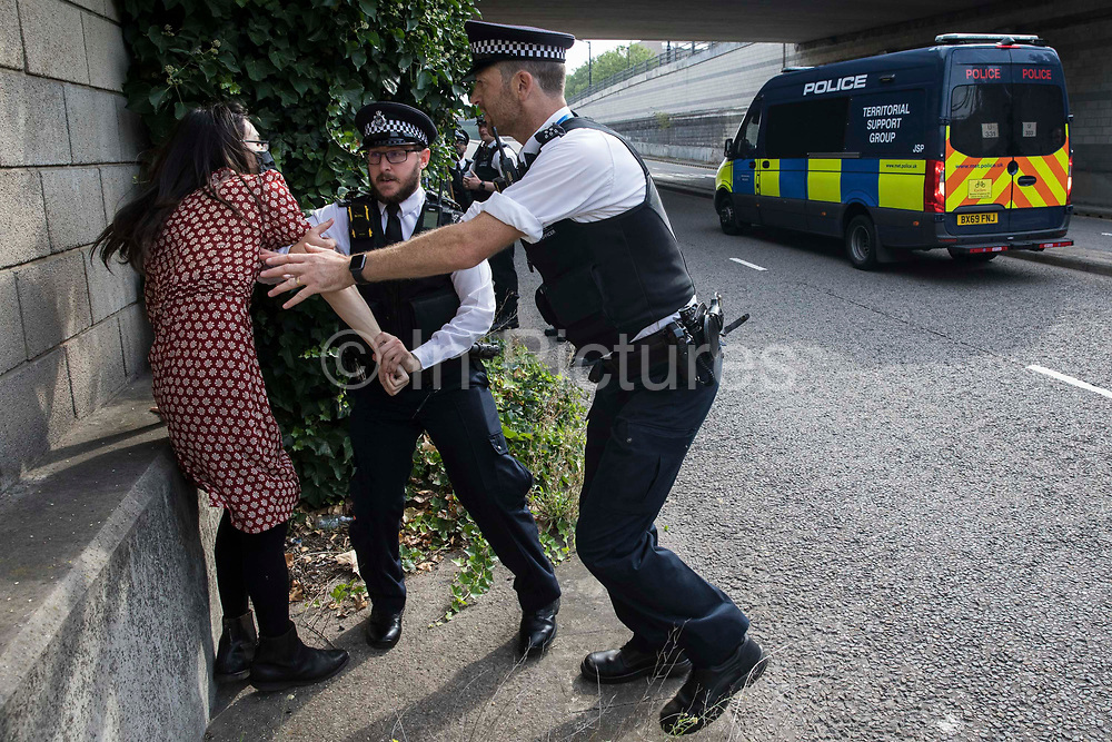Metropolitan Police officers restrain a human rights activist trying to run into an access road in front of a large military vehicle during a protest against the DSEI 2021 arms fair at ExCeL London on 6th September 2021 in London, United Kingdom. The first day of week-long Stop The Arms Fair protests outside the venue for one of the worlds largest arms fairs was hosted by activists calling for a ban on UK arms exports to Israel.