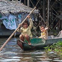 Children driving a boat on the Tonle Sap Lake near the Kompong Phluk floating village.
