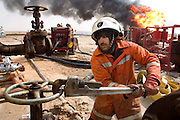 "Firefighters from the Kuwait Oil Company (called KWWK: Kuwait Wild Well Killers) connect hoses to water tanks and pumps by the second oil well fire they were working on in Iraq's Rumaila Oil field. Later in the day they failed to extinguished this fire with water and then tried to stop the flow of gas and oil with drilling mud using what is called a ""stinger"", a tapered pipe on the end of a long steel boom controlled by a bulldozer. Drilling mud, under high pressure, is pumped through the stinger into the well, stopping the flow of oil and gas. This was also unsuccessful. The Rumaila field is one of Iraq's biggest oil fields with 5 billion barrels in reserve. Many of the wells are 10,000 feet deep and produce huge volumes of oil and gas under tremendous pressure, which makes capping them very difficult and dangerous. Rumaila is also spelled Rumeilah.."
