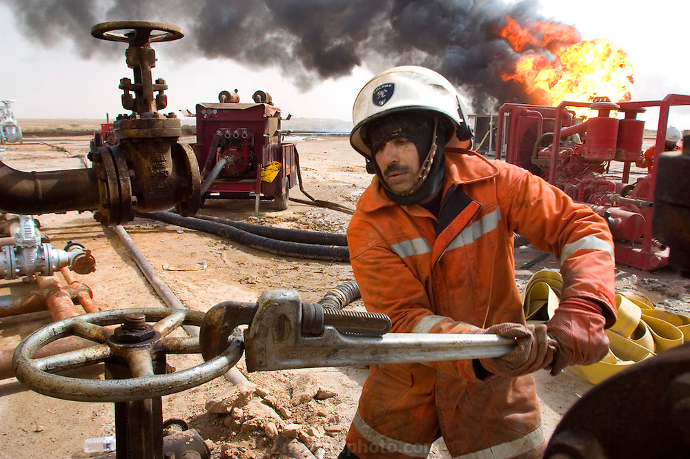 """Firefighters from the Kuwait Oil Company (called KWWK: Kuwait Wild Well Killers) connect hoses to water tanks and pumps by the second oil well fire they were working on in Iraq's Rumaila Oil field. Later in the day they failed to extinguished this fire with water and then tried to stop the flow of gas and oil with drilling mud using what is called a """"stinger"""", a tapered pipe on the end of a long steel boom controlled by a bulldozer. Drilling mud, under high pressure, is pumped through the stinger into the well, stopping the flow of oil and gas. This was also unsuccessful. The Rumaila field is one of Iraq's biggest oil fields with 5 billion barrels in reserve. Many of the wells are 10,000 feet deep and produce huge volumes of oil and gas under tremendous pressure, which makes capping them very difficult and dangerous. Rumaila is also spelled Rumeilah.."""