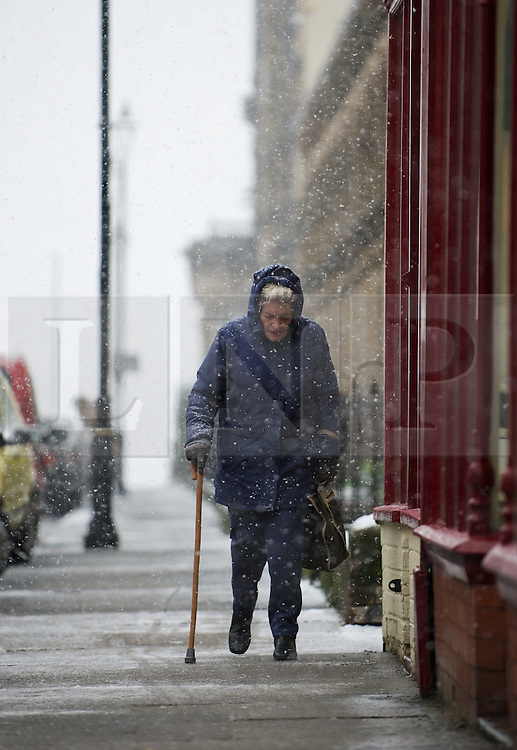 © Licensed to London News Pictures. 14/01/2013..Saltburn, Cleveland, England..An elderly woman makes her way through snowfall in Saltburn as parts of North Yorkshire and East Cleveland saw heavy snow fall today  ..Photo credit : Ian Forsyth/LNP