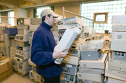 Man piling up worn out computers at recycling plant,