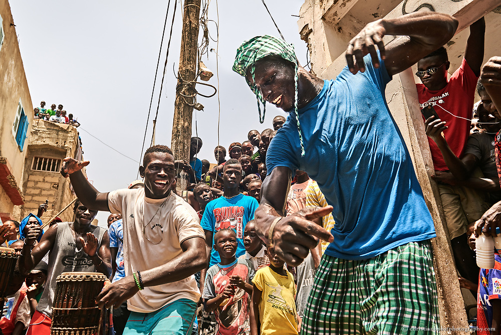 People of the village of Ngor in Dakar gather in front of the house of the family of Kherou Ngor, to see the young wrestler performing a traditional wrestling dance to the sound of drums before he goes to a fight at the Iba Mar Diop stadiumin Dakar on July 22, 2016. Dancing and drumming performances take place before every Senegalese wrestling fight and tournament.