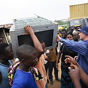 Electronic waste export to Nigeria...Alaba International Market, one of the largest markets for electronic goods in West Africa.  New and old - and a lot of non-working electronic goods such as TVs and computers come in to the market via Lagos harbour from the US, Western Europe and China...Eric Albertsen from Grrenpeace inspects the TV. ..The shipment - TV-set originally delivered to municipality-run collecting point in UK for discarded electronic products - was tracked and monitored by Greenpeace using a combination of GPS (Global Positioning System using satellites), GSM (positioning using data from mobile networks to triangulate approximate positions) and an onboard radiofrequency transmitter (used for making triangulations in combination with handheld directional receivers used by team on ground) is placed inside the TV-set.  The TV arrived in Lagos in container no 4629416.