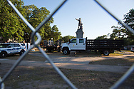 Jefferson Davis Monument behind a fence, guarded by New Orleans police.