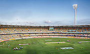 Players warming up and the ground being prepared before play in a T20 game at the Gabba.