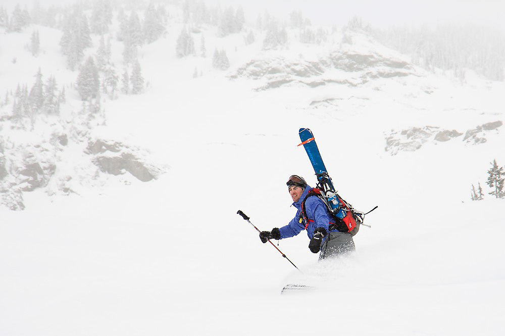 Lewis Rogers snowboards through deep powder in the backcountry, skis strapped to his backpack, in Mount Baker-Snoqualmie National Forest, Washington.