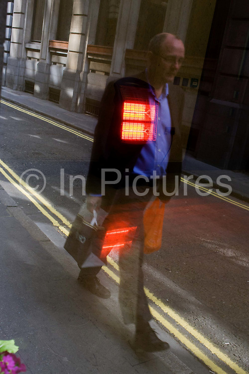 Man walks along narrow City of London lane, with reflection of office heater over his chest. Timed as he passes-by, the glowing heat radiates from the heater as if across his chest. He makes his way along a narrow medieval lane in the heart of the capital's financial district, known as the Square Mile, founded by the Romans in AD43.