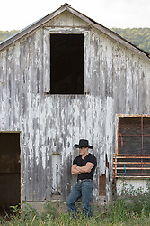 sexy cowboy in a black tee shirt leaning against an old wooden barn
