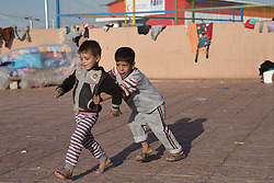 Licensed to London News Pictures. 22/10/2016. Two young Iraqi refugee boys, newly arrived from areas where the Mosul Offensive is taking place, play in the court yard of a school at the Dibaga refugee camp near Makhmur, Iraq. Upon arriving at the camp women and children stay in the school for around 10 - 15 days whilst completing the registration process.<br />