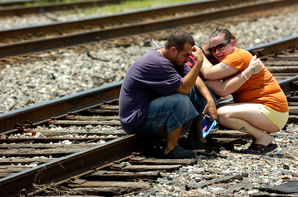 Lakeland.,Fl 7/17/07-Louis Marshall,left William Entrekin,(middle  ) and Jackie Hardy, right( hugging Entrekin) comfort each other as they remember the victim Brian Guy who was one of the victim in the train versus car accident in Lakeland.(Scott Iskowitz/ Tampa Tribune)