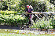 © Licensed to London News Pictures. 13/05/2015. Cliveden, UK. A couple look at the water garden.  Visitors to the National Trust property Cliveden House enjoy the warm and sunny weather today 13th May 2015. Photo credit : Stephen Simpson/LNP