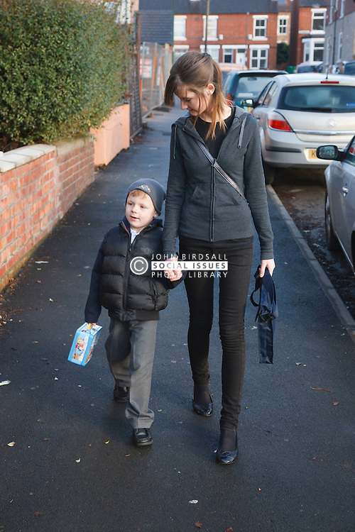 Teenage sister walking young brother to primary school