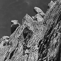 Roger Schley climbs a possible new route up the north face of Cleaver Peak in the Sawtooth Range of the Sierra Nevada. (1974)