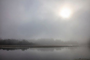 The sun shines through thick fog that has settled over Borst Lake in Snoqualmie, Washington.