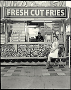 """Food worker Tara Jesperson sells fresh cut fries under the watchful eye of Meaghan Maloney an auditor with the Calgary Stampede. Jesperson loves being on the road with traveling fairs, this her 20th year. """"This is where I am home,"""" she says. Maloney, an accountant in the city during the year, audits cash coming in and out of the various venues during Stampede. Photograph by Todd Korol for The Globe and Mail"""